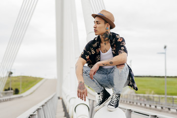 Young man crouching on railing of bridge