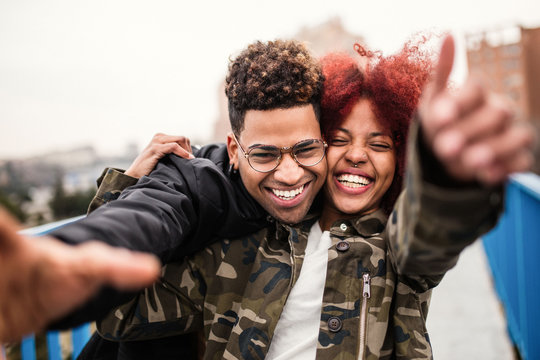 Cheerful black couple embracing and laughing