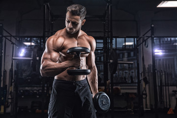 Young handsome sportsman bodybuilder weightlifter with an ideal body, after coaching poses in front...