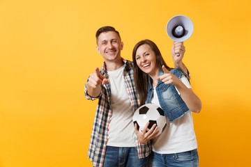Young happy cheerful couple supporter, woman man, football fans cheer up support team, holding megaphone, soccer ball isolated on yellow background. Sport, family leisure, people lifestyle concept.