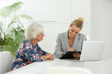 businesswoman having financial meeting with retired customer