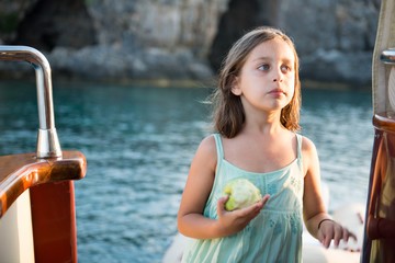 cute girl is eating her apple on the boat
