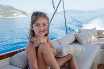 cute girl is smiling and sitting on boat