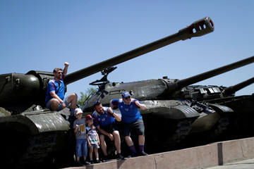 Iceland's supporters take a picture in World War II era tanks on the banks of Volga river in Volgograd
