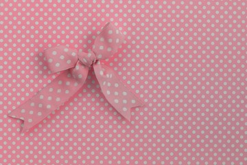 Pink ribbon on polka dots.