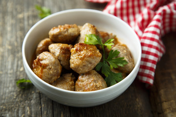 Homemade meatballs with fresh parsley in a white bowl