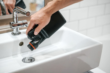 Removal of blockage in the sink, the hand of a man with a bottle of a special remedy with granules. Clean the blockages in the bathroom with chemicals.