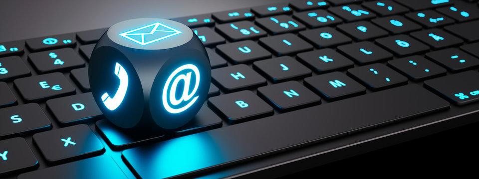 Leuchtender Würfel mit Kommunikations-Symbolen auf Tastatur