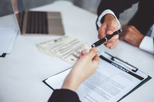 Businessman giving pen to businesswoman for signing contract banking money loaning
