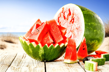 Summer photo of watermelon on white wooden table and sea landscape with blue sky. Free space for your decoration.