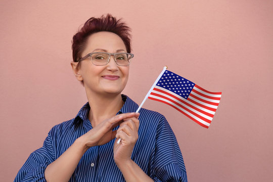 American flag. Woman holding USA United States flag. Nice portrait of middle aged lady 40 50 years old with a national flag over pink wall background. Learn English language. Visit USA concept.