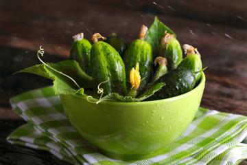 свежие огурцы в зеленой миске с листьями и каплями воды