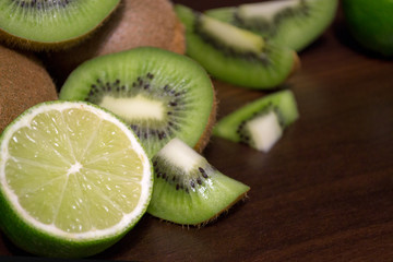 Sliced kiwi with lime on a dark brown wooden table