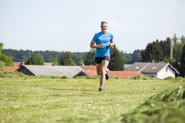 Mature man running on meadow