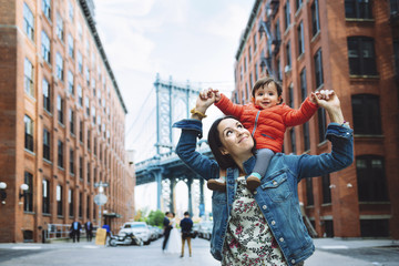 Mother and baby in Brooklyn with Manhattan Bridge in background, NYC, USA
