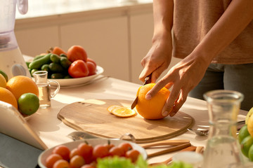 Unrecognizable woman in casualwear cutting ripe fresh orange while preparing ingredients for healthy smoothie