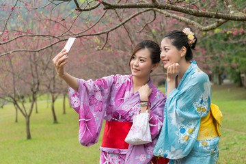 young Asian females taking selfie together