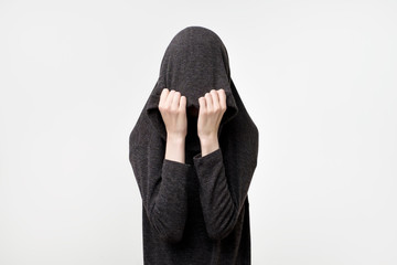 Woman hiding face under the clothes. She is oulling sweatr on her head. Depressed emotion.