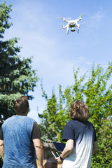 Father and son on summer day flying drone on countryside.