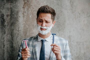 Businessman shaves his face, getting ready for business meeting. Advertising of shaving accessories
