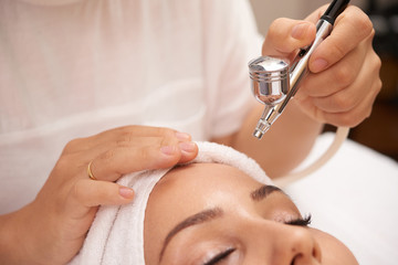 Master of beauty salon holding laser device over face of young client before cosmetic procedure