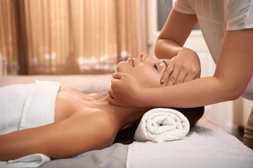 Young woman having calming massage on her face while relaxing in luxurious spa salon