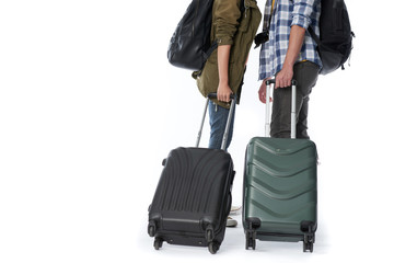 Close-up shot of male and female tourists pulling heavy suitcases, isolated on white background