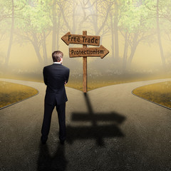 """Businessman stands on crossroad between """"free trade"""" and """"protectionism"""""""
