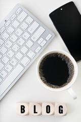 Würfel mit dem Wort BLOG am Arbeitsplatz mit Tastatur und Kaffee
