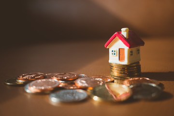 Miniature house on stack coins using as business and financial concept