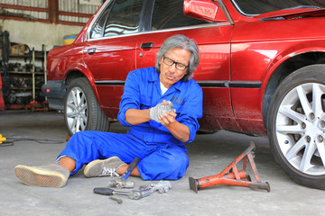 Car mechanic feeling pain in her hand After accident at work in auto repair service