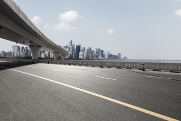 asphalt road with city skyline