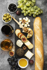 Snacks with wine - various types of cheeses, figs, nuts, honey, grapes, bread on a gray background. Top view. Food background