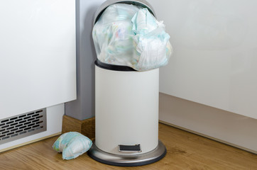 garbage can full of  used dirty diapers .