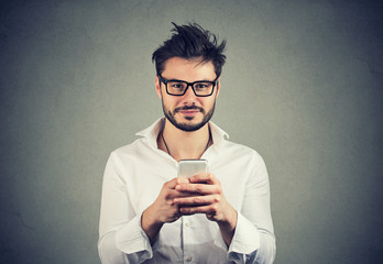 Happy hipster man in glasses using a smartphone