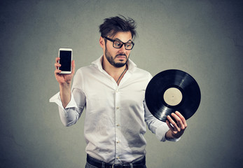 Confused man with vinyl and smartphone