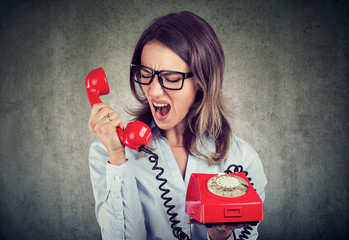 angry enraged business woman yelling at the red telephone