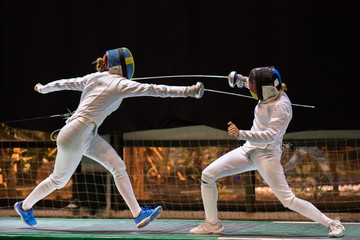 Two woman fencing athletes fight