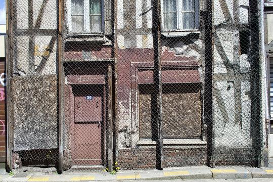 Vieille maison recouverte d'un filet d'acier anti chute de pierre et anti squat