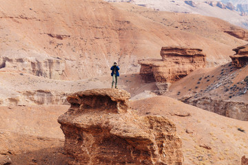 A cheerful traveler with a camera stands on the edge of the cliff in the Charyn canyon in Kazakhstan.