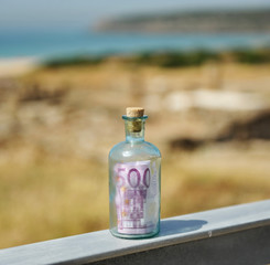 Old glass bottle with 500 euro inside. Tax havens and offshore banking concept