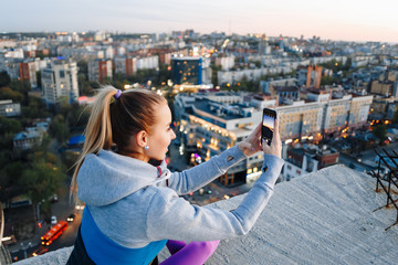 Young girl in sports uniform takes photos on the phone on the roof of a building over the city