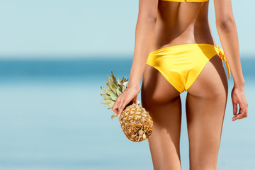 cropped image of woman in bikini holding pineapple in front of sea