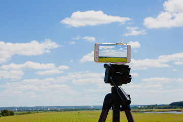 Smartphone on tripod capturing summer landscape