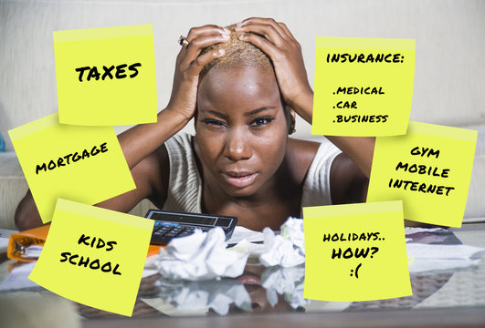 desperate and frustrated black afro american woman domestic accounting worried about money paying taxes calculating expenses and payments