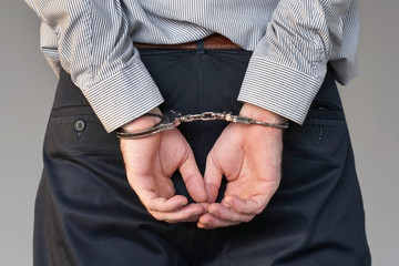 Close-up. Arrested man handcuffed hands at the back. Isolated on gray background. Businessman in office in handcuffs holding a bribe. Arrested man in handcuffs.