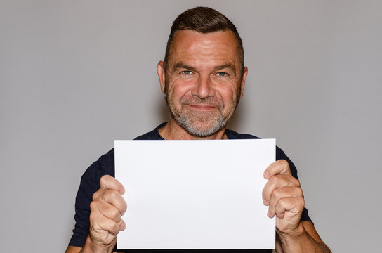 Attractive smiling middle-aged man holding a sign