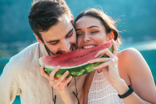 Cheerful couple holding slices of watermelon