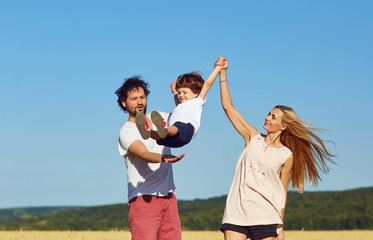 A happy family is enjoying fun with a child outdoors in a summer field.