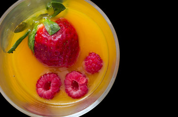 high view of non-alcoholic cocktail with strawberry and raspberry juice with black background